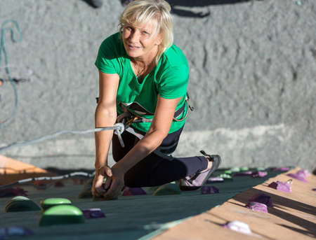 belaying: Portrait of Adult Female Climber Moving Up on Sport Training Course in Outdoor Climb Gym Using Rope and Belaying Gear