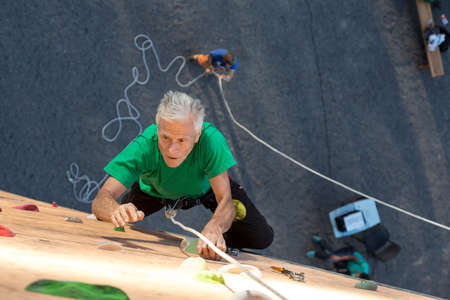belaying: Aged Climber Makes Hard Move on Outdoor Vertical Gym Sporty Clothing Intense Emotional Face Belaying Partner on Background