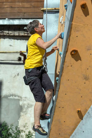 ascending: Elderly Female Demonstrates Excellent Physical and Mental Abilities Ascending Vertical Climbing Wall