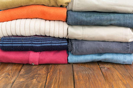 neatly stacked: Natural Wooden Board Desk with Many Colorful Clothing Neatly Stacked in Two Rows Stock Photo