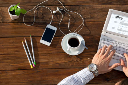websurfing: Top View of Man Typing on Laptop and Coffee Mug at Warm Natural Wood Table with Electronic Gadgets and Stationery Tools for Every Day Life