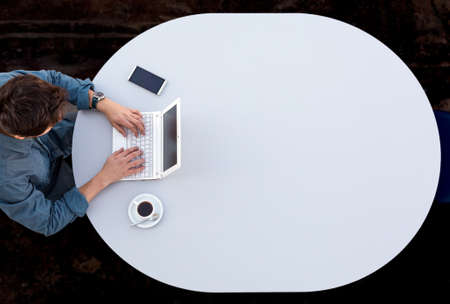 casual clothing: Grey Office Round Table and Man Working on Computer Top View Casual Clothing Typing on Keyboard with Marketing Chart on Screen Stock Photo