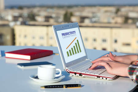 distant work: Female Hands Typing on White Laptop Keyboard at Roof Top Cafe Terrace with Urban Landscape on Background and Colorful Chart on Screen Stock Photo