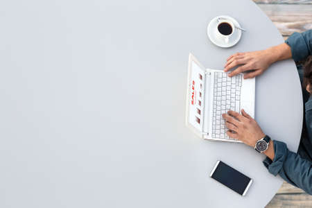 hombre tomando cafe: Oficina Gris Mesa Redonda y el hombre trabaja en el ordenador Vista superior Typing Vestimenta informal en el teclado con la carta de Marketing en la pantalla del teléfono inteligente