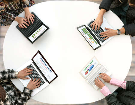 White Office Round Table and Men and Women Working on Computer Top View Casual Clothing Typing on Keyboard Many Laptops