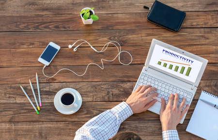 Natural bureau en bois brut et homme travaillant sur ordinateur Top Voir le produit Smart Casual Chart Vêtements Productivité sur Smart Phone Screen et tasse de café de côté