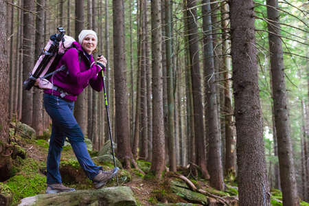 trekking pole: Female Hiker Staying inside Deep Old Forest on Moss Stone with Backpack and Trekking Pole Smiling and Joyful