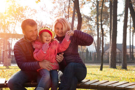 laughing out loud: Young Family of Three People Father Mother Little Baby Daughter Sitting in Autumnal Park Outdoor Laughing out Loud with Back Light Sun Shining