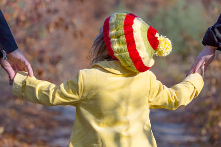 two generation family: Two Generation Family Walking in Autumnal Forest Father Mother Holding Hands of Little Baby Girl Bright Yellow Clothing Coat and Cap Close Up Rear View
