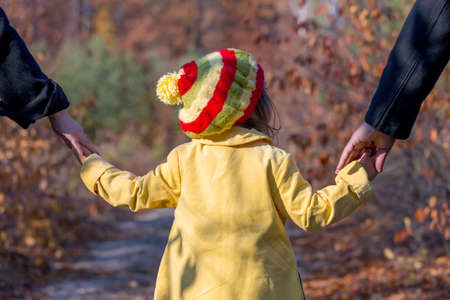 two generation family: Two Generation Family Walking in Autumnal Forest Father Mother Holding Hands of Little Baby Girl Bright Yellow Clothing Coat and Cap Rear View Stock Photo