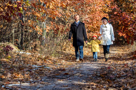 two generation family: Two Generation Family Walking in Autumnal Forest Alley Father Mother Holding Hands of Little Baby Girl Bright Yellow Clothing Coat and Cap Front View