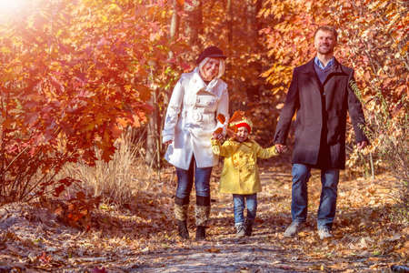 Two Generation Caucasian Family Walking in Colorful Autumnal Forest Alley Smiling Father Mother Holding Hands of Little Baby Girl Casual Clothing Sun Shining