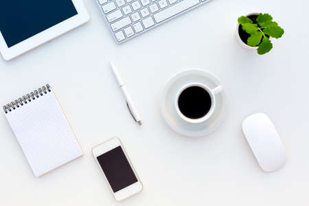 Top View of White Office Desk with Modern Electronics Computer Keyboard Tablet Telephone Notepad Pen Coffee Cup and Green Flower