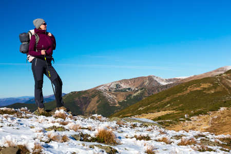 walking pole: Energetic Female Hiker Staying on Snowy Terrain and Observing Scenic Mountain View Sporty Clothing Jacket and Pants Backpack and Walking Pole