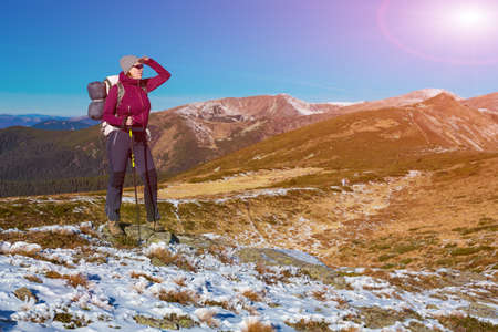 walking pole: Energetic Female Hiker Staying on Snowy Terrain and Observing Scenic Mountain View Backpack and Walking Pole Sun shining from blue sky Stock Photo