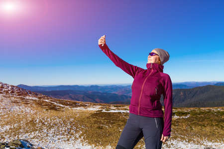 self   portrait: Cute Woman in sporty Clothing making self portrait selfie on mobile Phone Mountains View and Sun Shining
