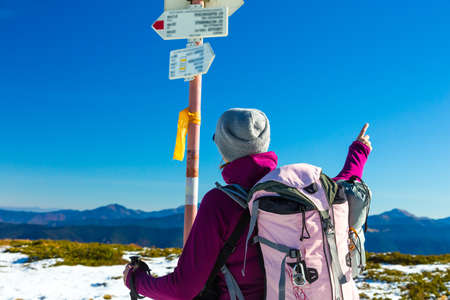 trail sign: Hiker with Backpack Staying and Looking on Trail Sign sporty Clothing blue Sky