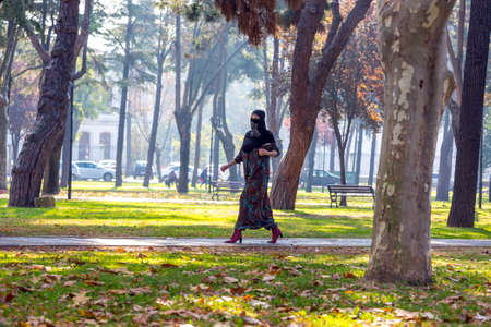modesty: An attractive Young woman wearing a colorful head covering and Muslim Dress Walking in University Park