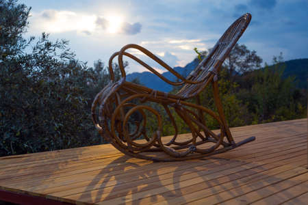 rocking chair: Vintage wooden Rocking Chair at lumber Cottage Terrace Patio Forest and Mountains Sunrise