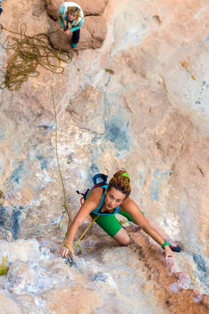 belaying: Top View of cute female Climber looking up ascending colorful rocky Wall and her belaying Partner