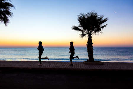 joggers: Two People Man and Woman jogging on Seafront making Morning Fitness Tropical Palm Tree colorful Dawn blue Sea. Focus on Palm Tree and paved path, joggers body slightly blurred in motion