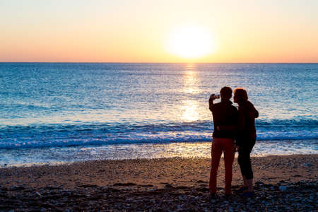 self   portrait: Man and Woman staying on Beach and taking self portrait on telephone bright sunrise and Sea surf