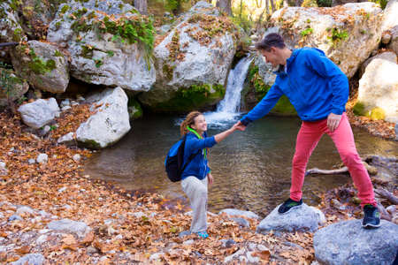 shaking out: Two Hikers young Man and Smiling Woman holding hands helping each other walking mountain stream with waterfall