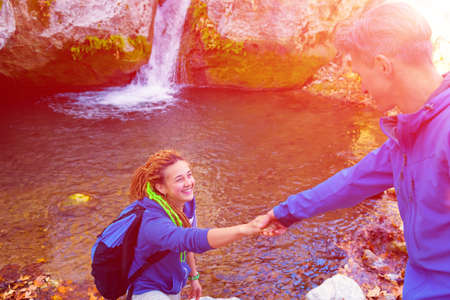shaking out: Two Hikers young Man and Smiling Woman holding hands helping each other walking mountain stream with waterfall and Sun shining