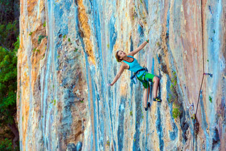 safety gear: Young Female Climber ascending vertical rocky wall sporty Clothing Blue Shirt Green Pants using Rope and other Safety Gear Stock Photo