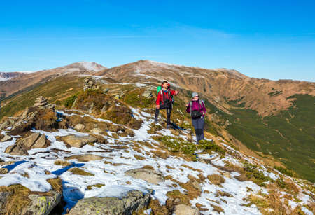 observing: Two Hikers staying on winter Mountain terrain pointing observing Landscape Snow and grassy Trail Backpacks and walking Poles