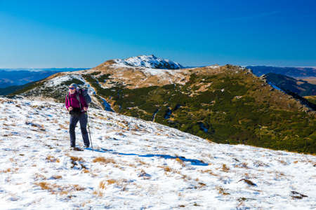 wintersport: Female Hiker with Backpack walking up on Snow Slope Mountains View blue Sky sunny Day Stock Photo