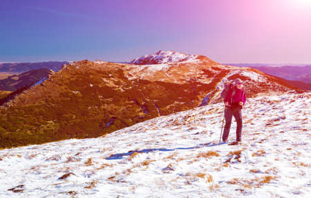 wintersport: Female Hiker with Backpack walking up on Snow Slope Mountains View blue Sky Sun shining Stock Photo