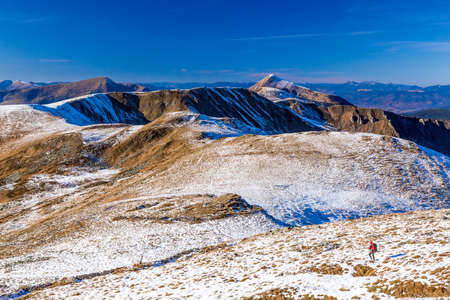 wintersport: Hiker Man with Backpack walking on Snow Slope Trail Mountains View blue Sky sunny Day Bright sporty Clothing red Jacket Stock Photo