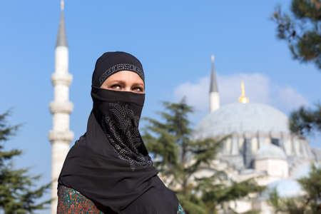 minarets: Portrait of beautiful Arabian Woman in traditional Muslim Clothing Middle East Urban landscape with Mosque and Minarets on Background