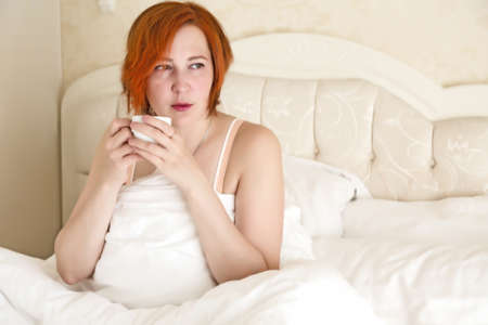 queen bed: Woman in Queen Size Vintage Bed drinking Morning Coffee white Cup white Blanket warm tone background