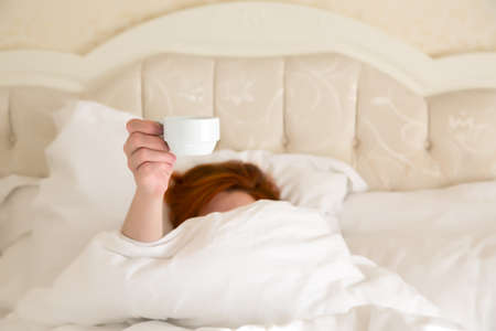 queen bed: Female hand holding white Coffee Cup Queen Size Vintage Bed demanding her Morning Coffee white Blanket warm tone background