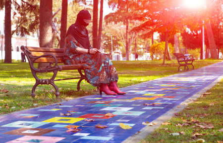 Colorful Alley at Park and Middle East Muslim Style dressed Lady sitting on bench reading making hand notes with Sun shining