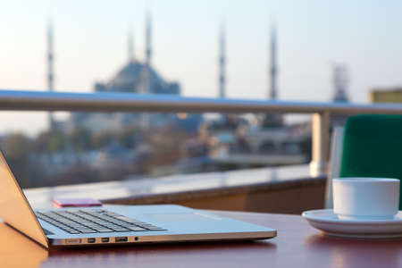 telecommuting: Breakfast Table of travelling Hipster with Laptop and Telephone Coffee Mug and Istanbul attraction Mosque on blurred Background Stock Photo