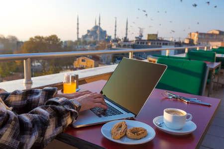 Werken Ontbijt Persoon die aan laptop computer in Cafe Terrace op tafel met Beker van Orange Juice and Bakery Cookies Aziatische Urban Landscape Moskee
