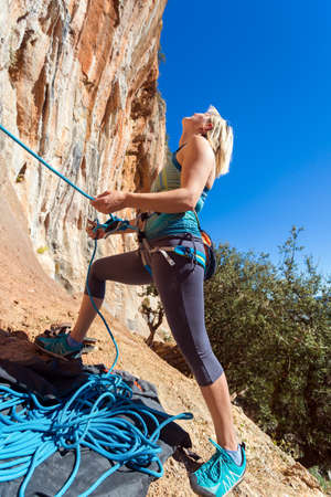 belaying: Blond Female Athlete belaying her Climbing Partner with Rope staying at orange rocky overhanging wall blue Sky