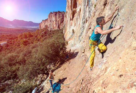 belaying: Team of Climbers Man and Woman ascending orange bright rocky Wall with rope and gear Male Leading Female belaying blue Sky and green Forest Stock Photo