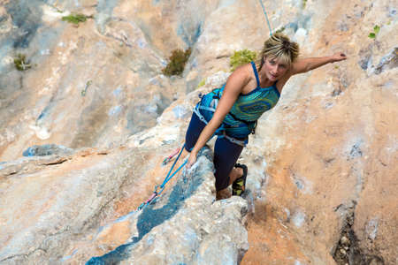 rapelling: Portrait of Cute Woman doing Exercise climb natural rock preparing for next Move Top View Stock Photo