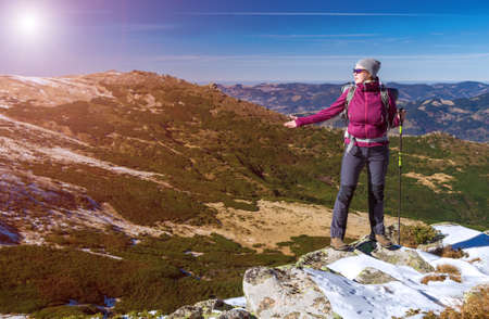 admiring: Female Hiker standing on snowy Rocks admiring scenic Winter Mountain View carrying Backpack and walking Pole Sun shining