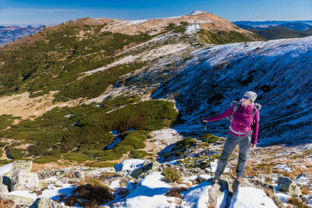 walking pole: Female Hiker standing on snowy Rocks admiring scenic Winter Mountain View carrying Backpack and walking Pole Stock Photo