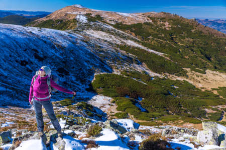 conquering adversity: Female Hiker standing on snowy Rocks admiring scenic Winter Mountain View carrying Backpack and walking Pole Stock Photo