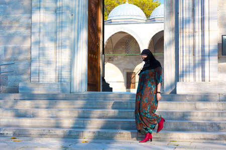 Islamic Style dressed eastern Woman walking on Marble stairs of Mosque outdoors Stock Photo