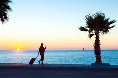 Exotic Vacation Silhouette of Female pulling Travel Suitcase on Seafront Alley Luminous Sunrise on Background tropical Tree