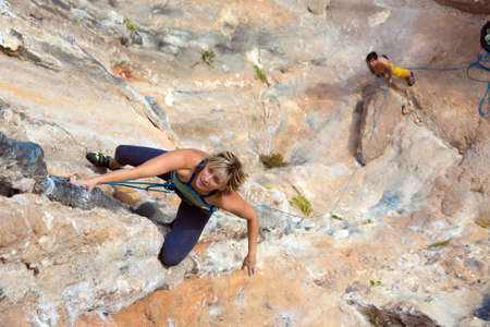 belaying: Beautiful Blond female Climber hanging on vertical Rock Wall her male Partner watching and belaying downstairs