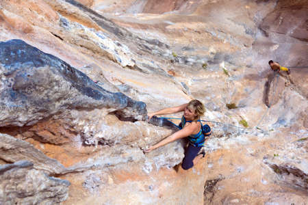 belaying: Beautiful Blond female Climber hanging on vertical Rock Wall her male Partner watching and belaying far downstairs Stock Photo