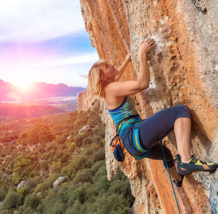 Female Climber Trying keep Hold Effort to avoid deep fall down High rocky Wall in orange and blue Colors Forest Mountains and Sky on Background Stockfoto
